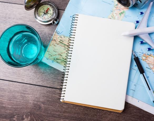 Kompas, szklanka z wodą, notes, mały samolocik plastikowy, notes i długopis oraz mapa na stole drewnianym